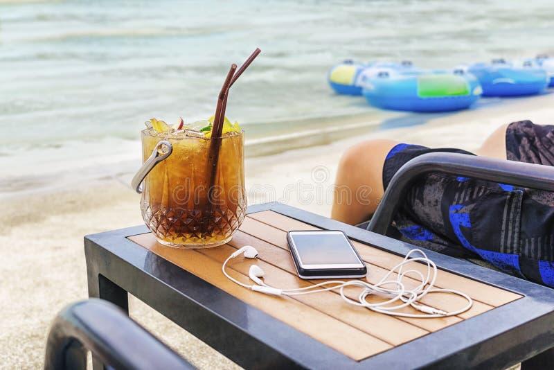 Человек сидя на пляже с ведром, сотовым телефоном и earpods коктейля на таблице Запачканное море и раздувные плавая кольца в back стоковое фото