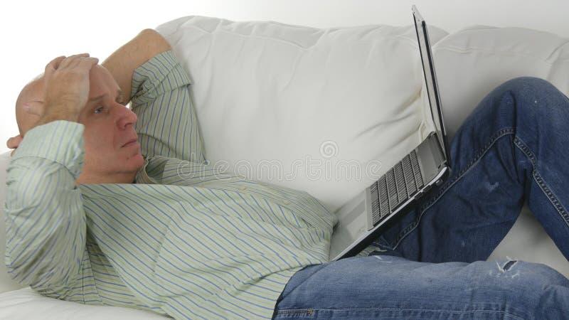 Человек сидя на софе делая дело используя ноутбук делает разочарованные жесты стоковая фотография