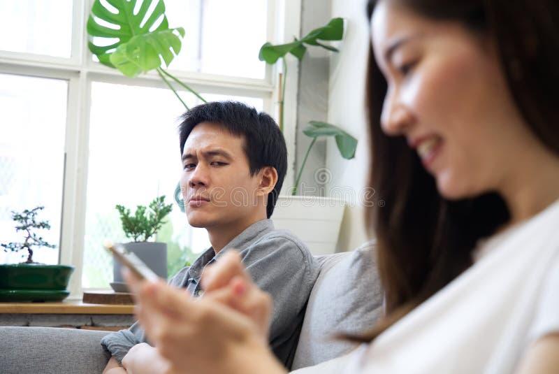 Человек сидя на софе чувствует сердитым с его девушкой стоковое фото rf