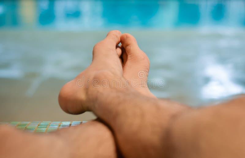 Человек сидя на стенде на крытом бассейне Перерыв выходных и ослабить стоковое фото