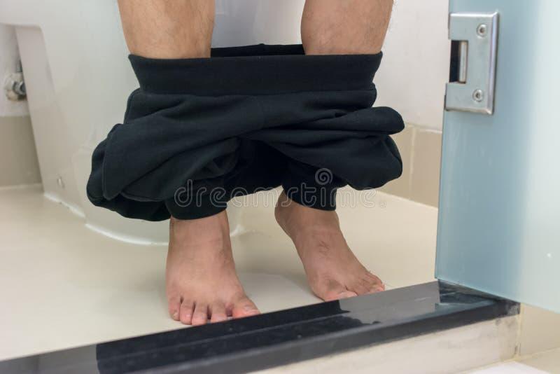 Человек сидя на туалете дома стоковая фотография rf