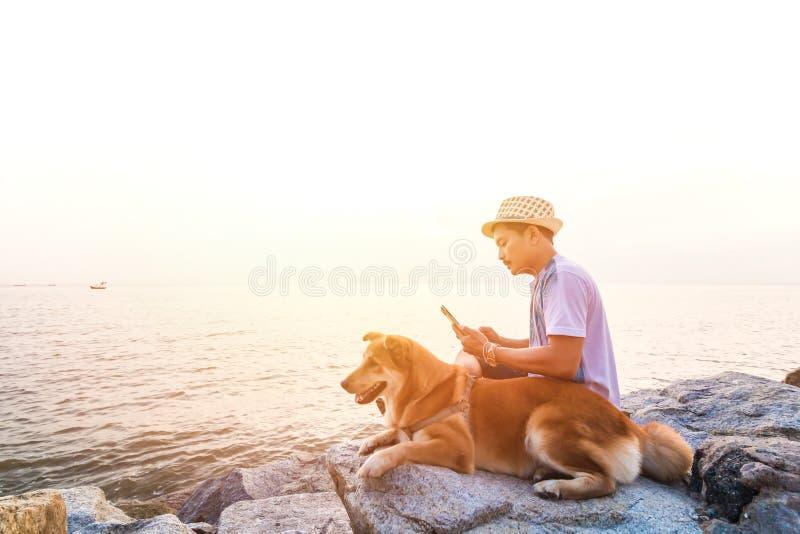 Человек сидя на утесах около любимчика и они около пляжа между заходом солнца стоковые изображения rf