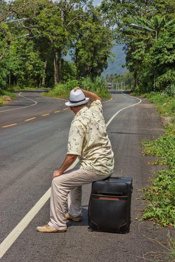 Человек сидя на чемодане стоковая фотография rf