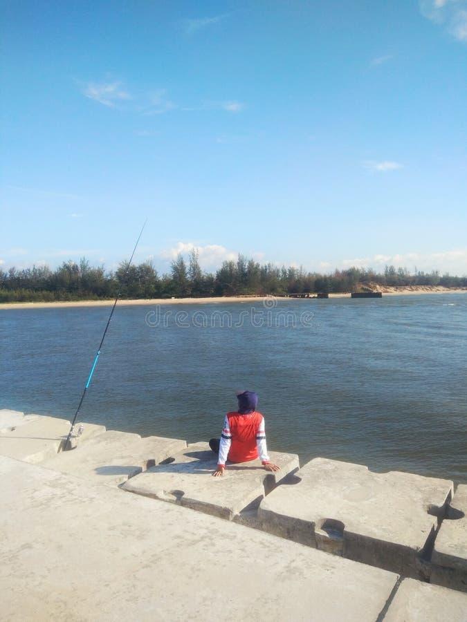 Человек сидя самостоятельно на рыбопромысловой деятельности на солнечный день - изображении пристани стоковые изображения rf