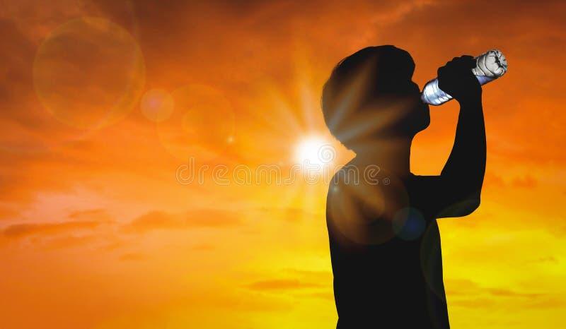 Человек силуэта бутылка питьевой воды на предпосылке жаркой погоды с сезоном лета Концепция высокой температуры и волны тепла стоковая фотография rf