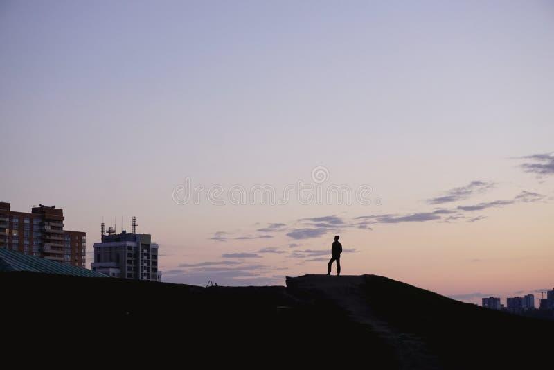 Человек силуэта стоит на холме против неба захода солнца вечера предпосылки голубого розового желтого стоковые фото