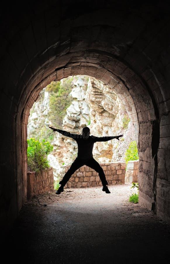 Человек скача в темный тоннель стоковые изображения rf