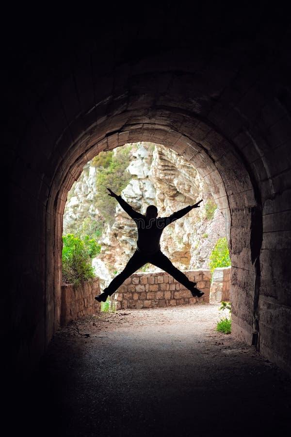 Человек скача в темный тоннель стоковые изображения