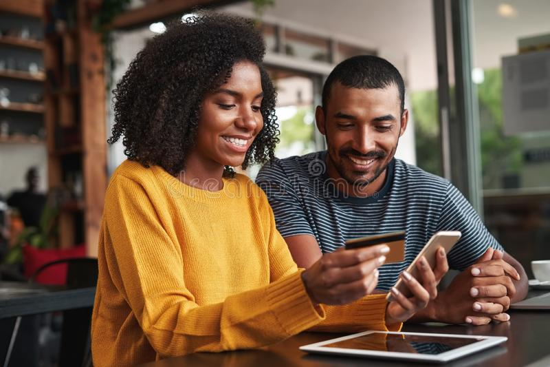 Человек смотря его покупки девушки онлайн в кафе стоковое изображение