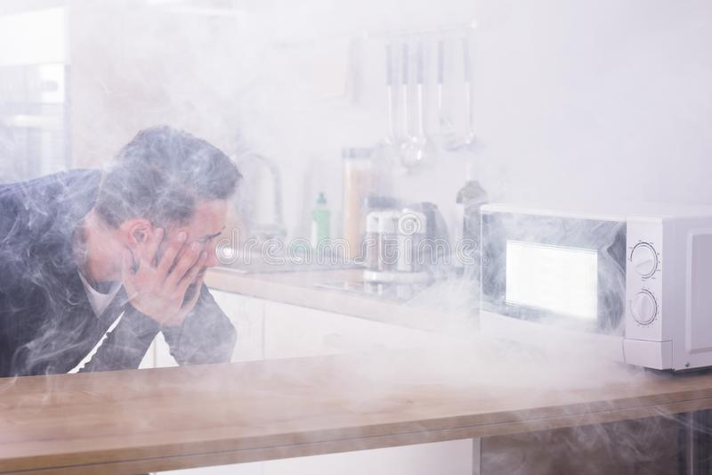 Человек смотря огонь приходя от микроволновой печи стоковое изображение