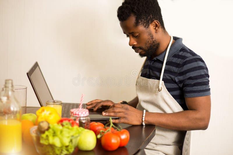 Человек смотря рецепт на ноутбуке в кухне дома стоковое фото