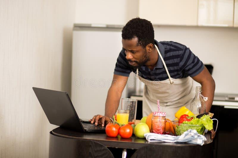 Человек смотря рецепт на ноутбуке в кухне дома стоковые изображения