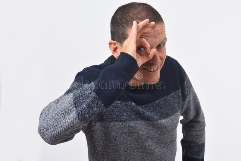 Человек смотря через пальцы если носящ стекла на белой предпосылке стоковая фотография rf