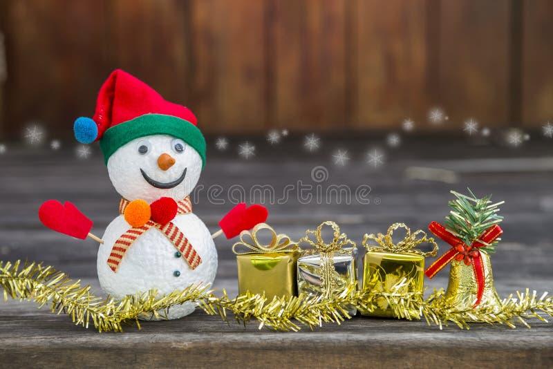 Человек снега с настоящим моментом и golen колокол над запачканным деревянным backgroun стоковое фото