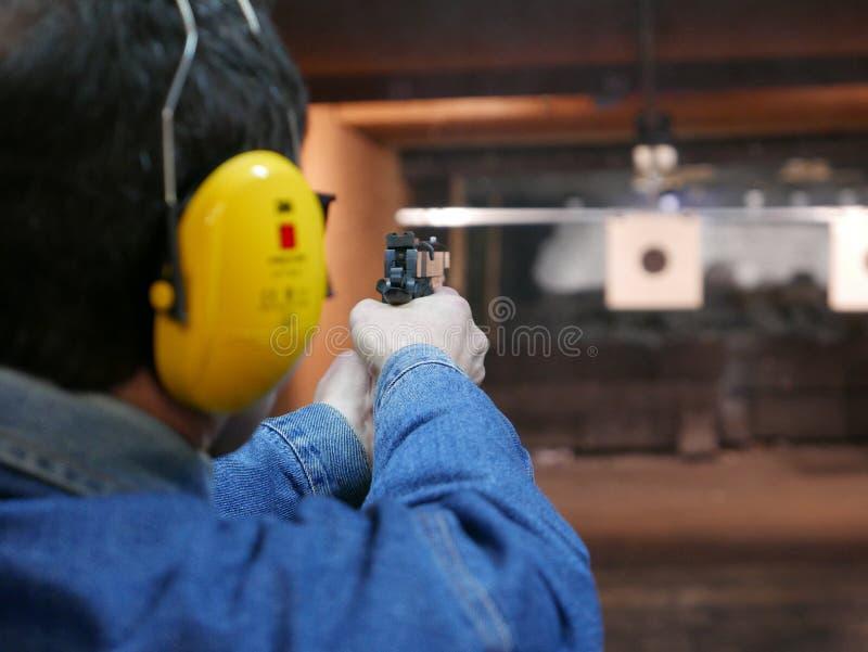 Человек снимая пистолет в стрельбище стоковые изображения rf