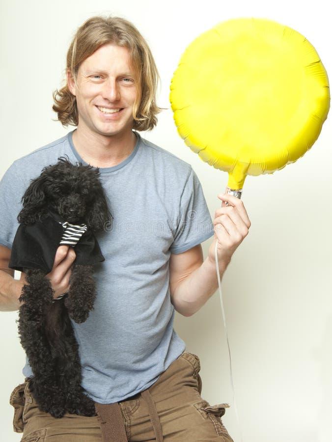 Человек, собака и желтый воздушный шар стоковое фото rf