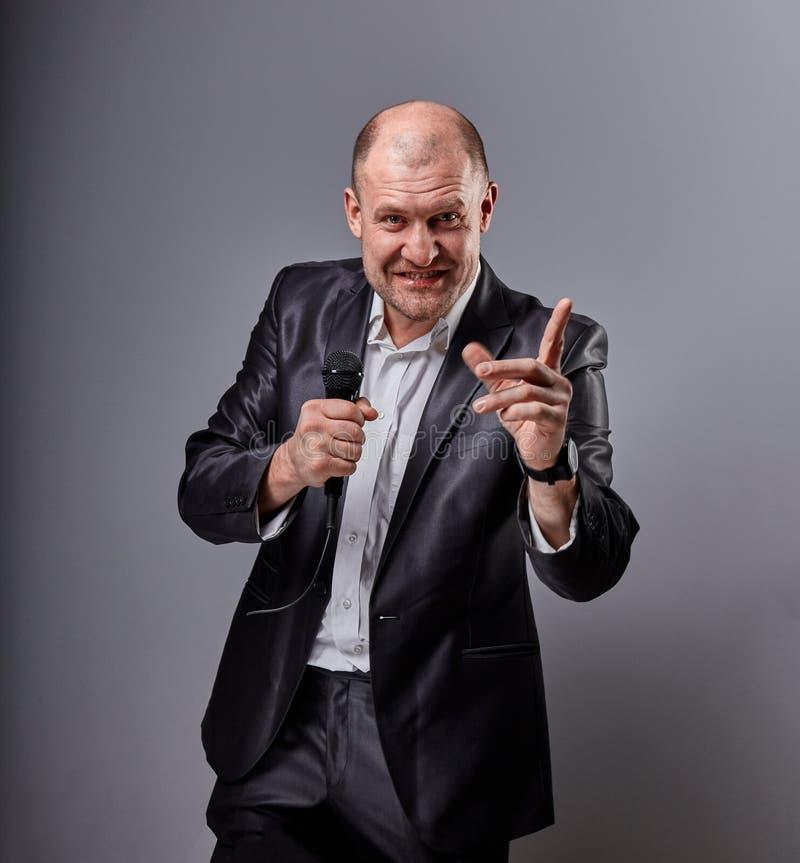 Человек совершителя потехи эмоциональный двигая счастливый представляя микрофон удерживания шоу в руке и показывая пальцу выбирая стоковые фотографии rf