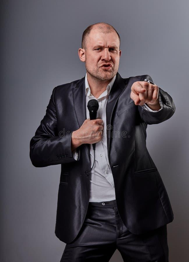 Человек совершителя потехи эмоциональный двигая счастливый представляя микрофон удерживания шоу в руке и показывая пальцу выбирая стоковые изображения rf