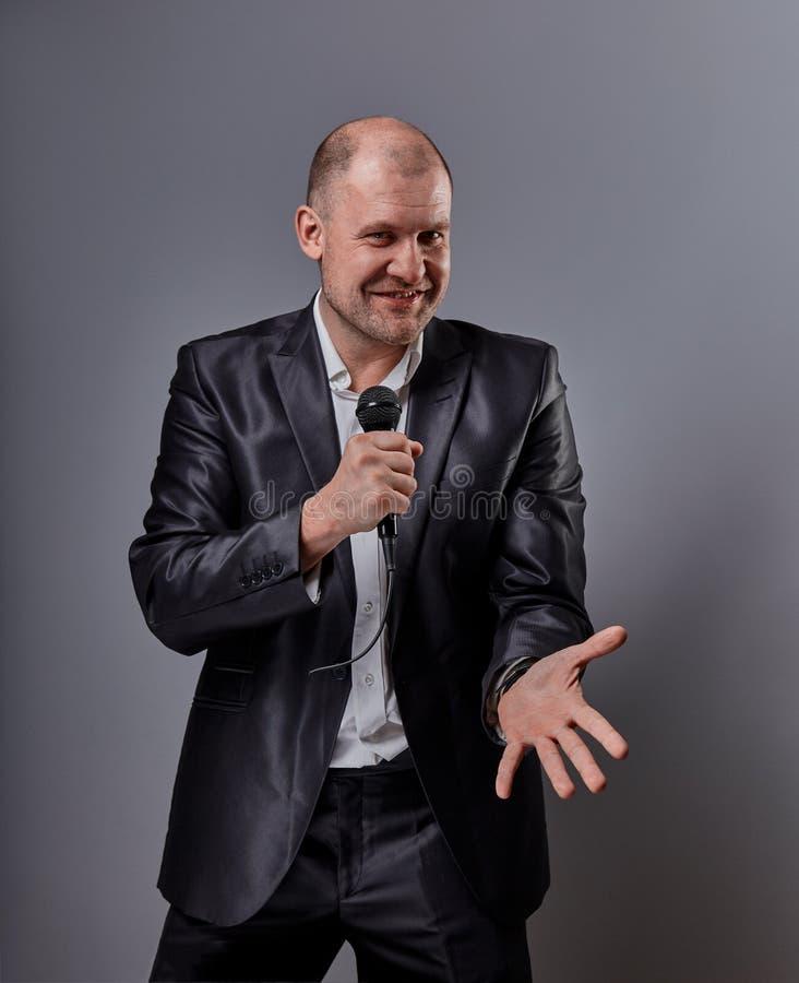 Человек совершителя потехи эмоциональный двигая счастливый представляя микрофон удерживания шоу в руке и показывая пальцу выбирая стоковое фото