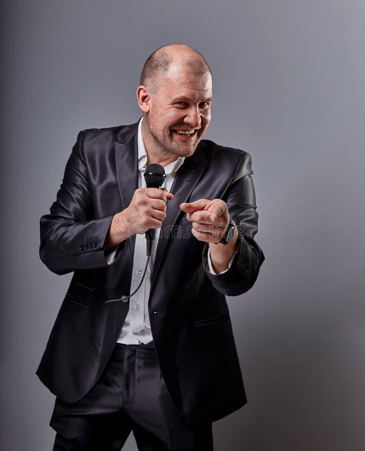Человек совершителя потехи эмоциональный двигая счастливый представляя микрофон удерживания шоу в руке и показывая пальцу выбирая стоковые фото