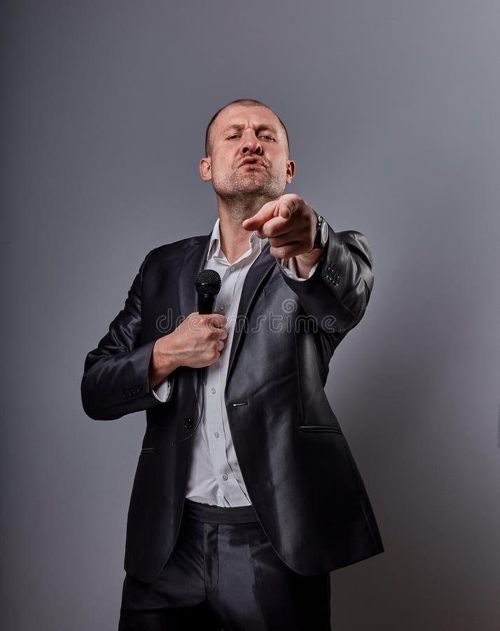 Человек совершителя потехи эмоциональный двигая счастливый представляя микрофон удерживания шоу в руке и показывая пальцу выбирая стоковая фотография rf