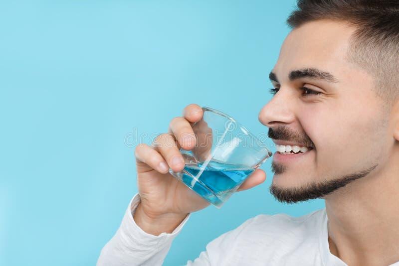 Человек со стеклом mouthwash на предпосылке цвета, космосе для текста Teethcare стоковая фотография