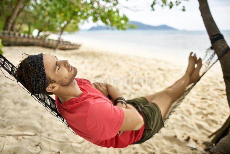 Человек со стерней лежит на черном гамаке на пляже песка стоковое фото
