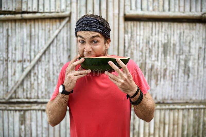 Человек со стерней со смешным выражением лица ест арбуз стоковое изображение rf