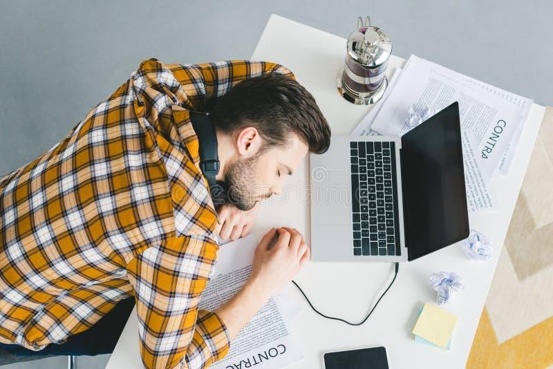 Человек спать на таблице с компьтер-книжкой стоковое фото rf
