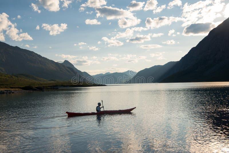 человек сплавляясь на каяке на национальном парке Норвегии Jotunheimen гребня Besseggen озера Gjende стоковое изображение