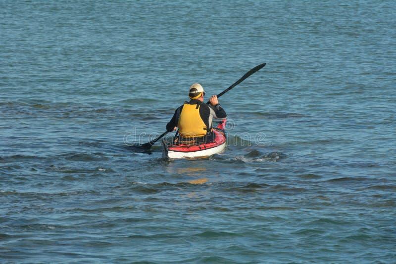 Человек сплавляясь на каяке с каяком моря стоковое изображение