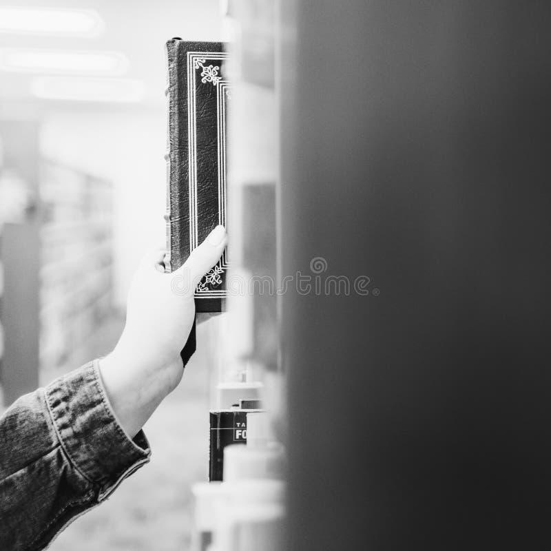 Человек сползая книгу от полки стоковое изображение rf