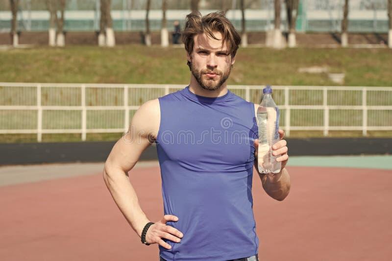 Человек спортсмена держа пластичную бутылку питьевой воды стоковая фотография rf