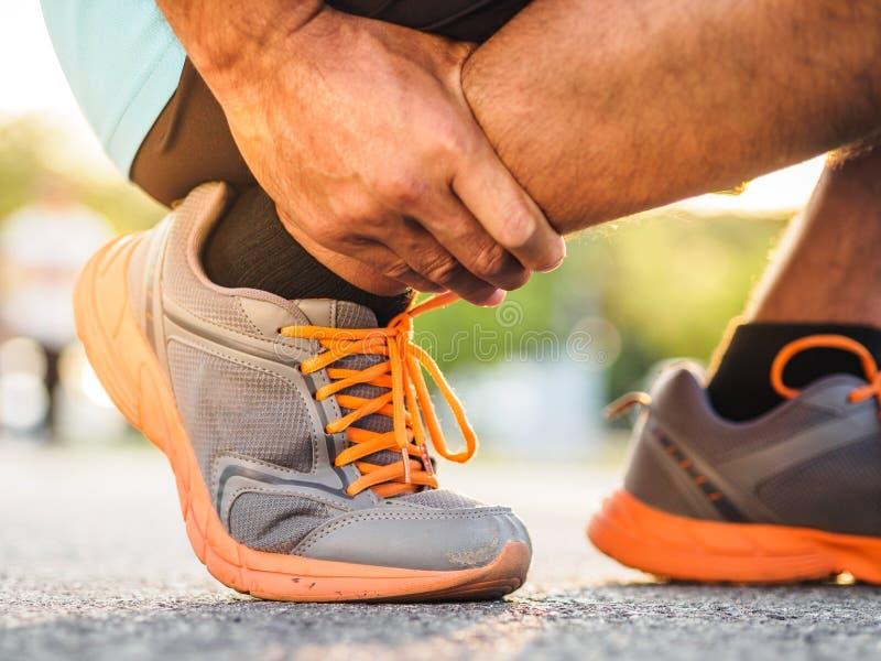 Человек спортсмена имеет травму лодыжки, sprained ногу во время идущего traini стоковая фотография