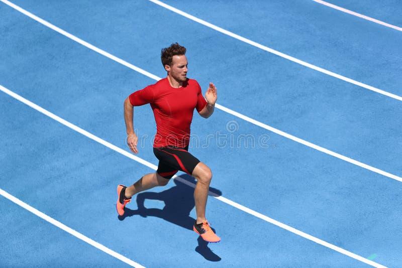 Человек спринтера бежать на голубых майнах следов в стадионе легкой атлетики в высокоскоростном взгляде сверху Мужской бегун спор стоковое изображение