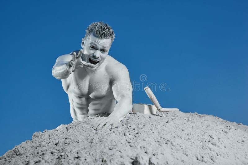 Человек среди серого песка кричащего и показывая вручную стоковые фотографии rf