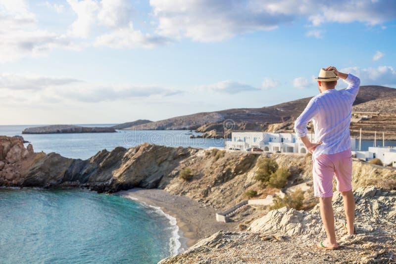 Человек стоит без сокращений на краю скалы смотря вне в расстояние к морю в утре на зоре стоковое фото rf