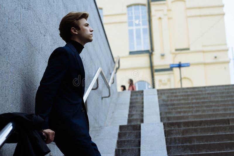 Человек стоит полагающся на серой стене о перилах, в темно-синем костюме, рядом с ним, на перилах, пальто висит, на стоковое изображение