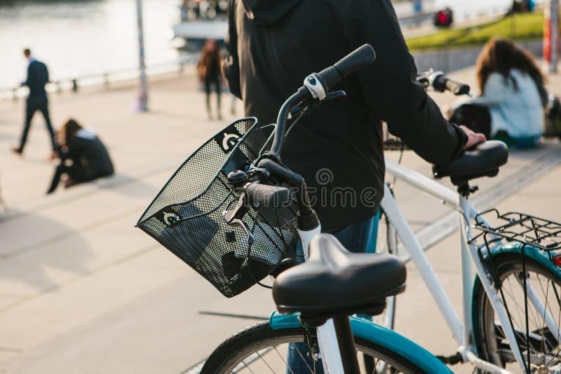 Человек стоит рядом с велосипедом в автостоянке велосипеда на обваловке в Берлине Запачканные люди на заднем плане стоковое фото