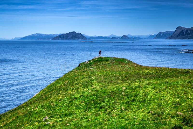 Человек стоя на пике горы обозревая норвежские побережье и Атлантический океан стоковые изображения