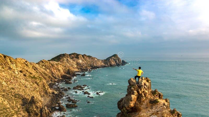 Человек стоя на пике горы океаном стоковая фотография