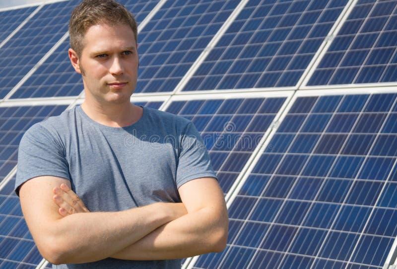 Человек стоя перед панелями солнечных батарей стоковые изображения rf