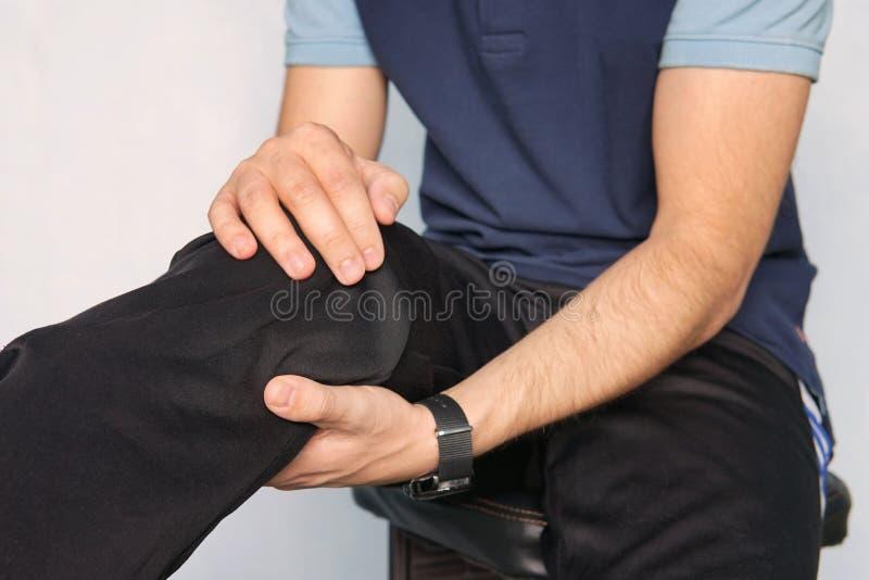 Человек страдая от боли колена молодой человек держит его руки над его больным коленом на голубой предпосылке трещиноватость pate стоковое фото rf