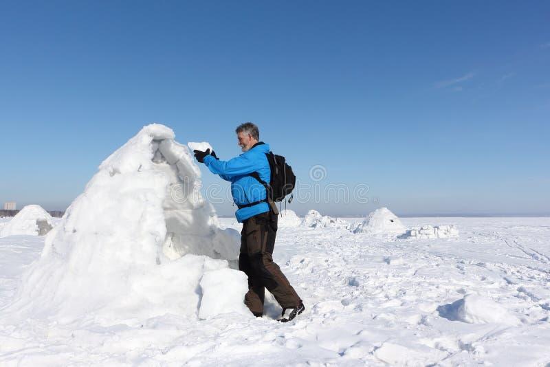 Человек строя иглу в зиме стоковые фото