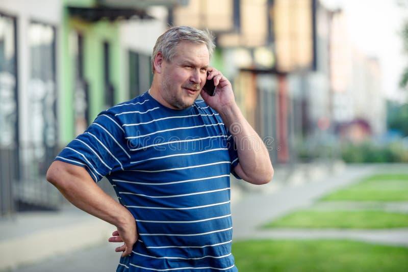 Человек счастливо говоря на смартфоне пока идущ на улицу стоковое фото rf
