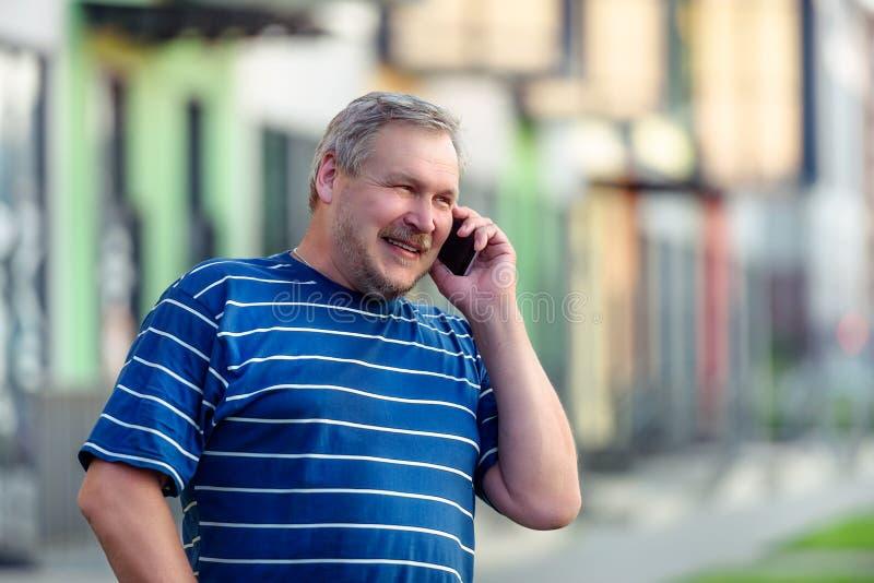 Человек счастливо говоря на смартфоне пока идущ на улицу стоковые изображения rf