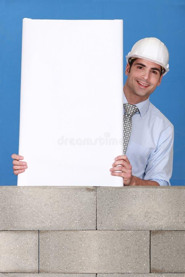 Человек с белой панелью на стене стоковое фото