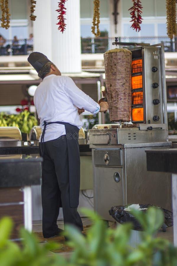 Человек с большим ножом варит Doner Shawarma в турецкой гостинице стоковое фото rf