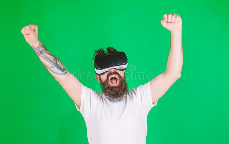 Человек с бородой в стеклах VR, зеленой предпосылкой Хипстер на крича стороне поднимая руки мощно пока взаимодействующий внутри стоковые фото