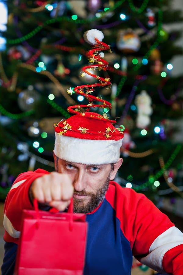 Человек с бородой в шляпе рождества на предпосылке дерева стоковая фотография rf